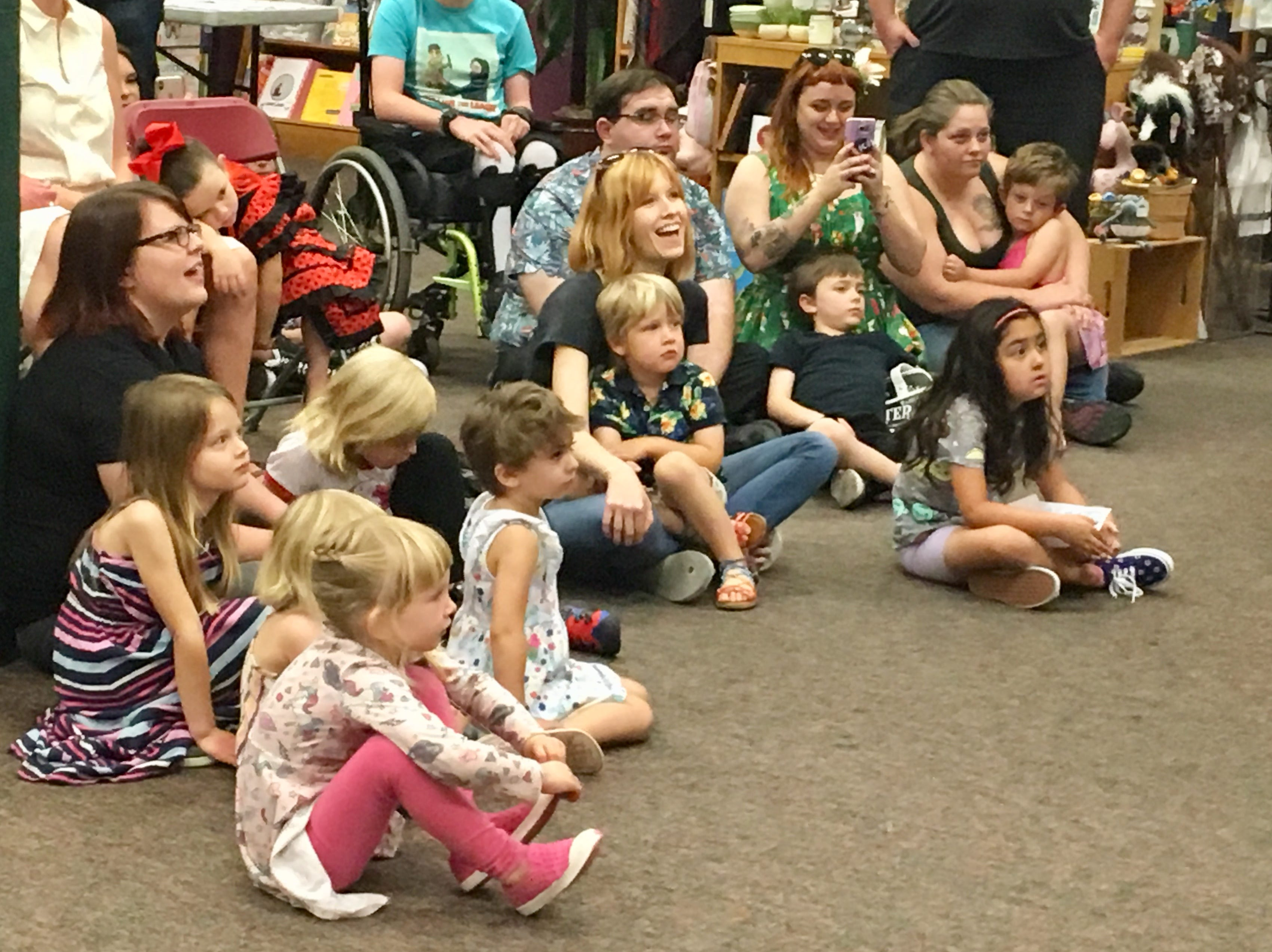 Molly Crum with son Seth, 3, on her lap listen to a story at Drag Queen Storytime at Changing Hands Bookstore in Tempe.