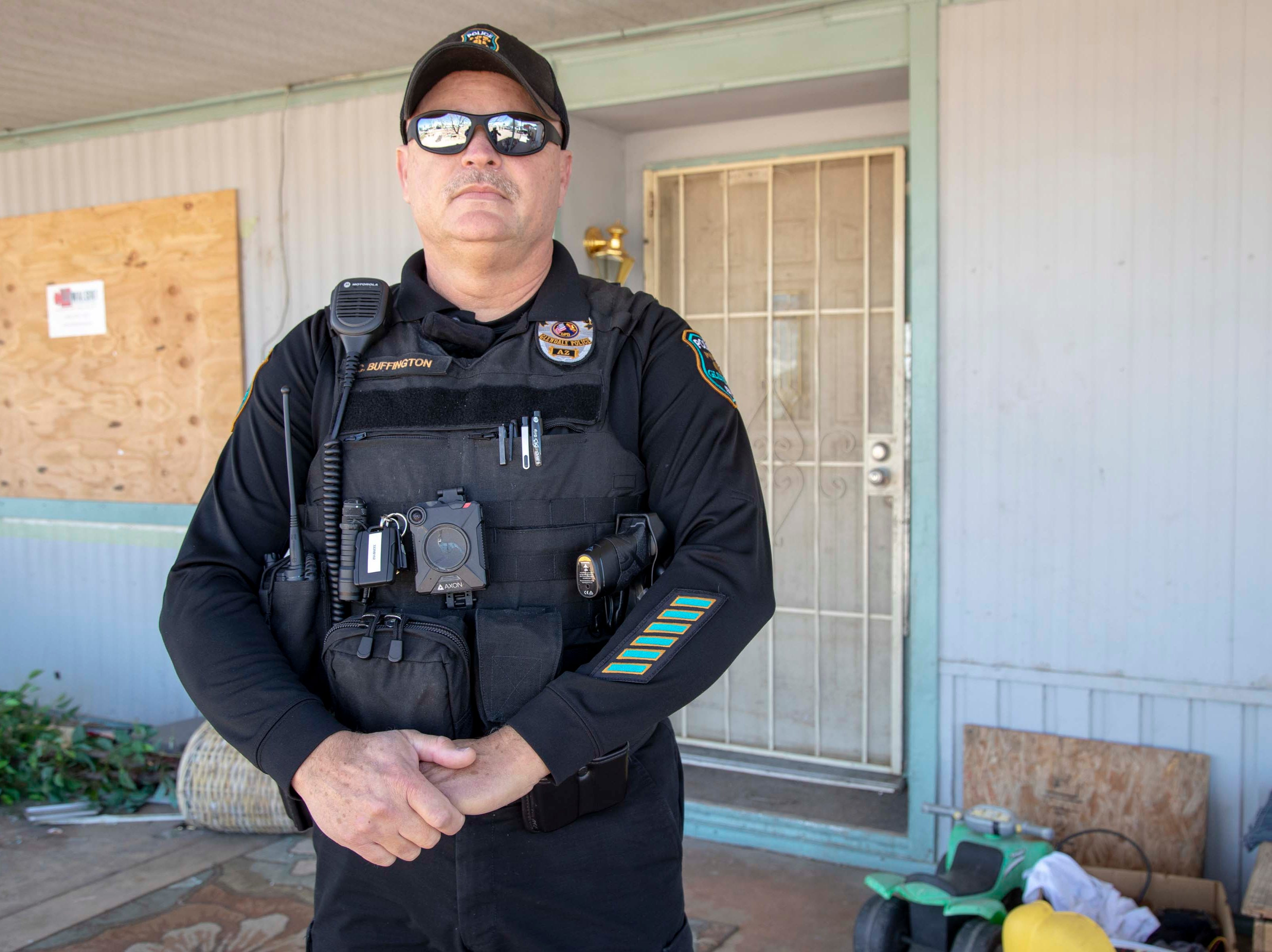 Glendale Police Officer Chuck Buffington stands in front of a vacant home in Granada Estates. Buffington is trying to clean up the neighborhood.