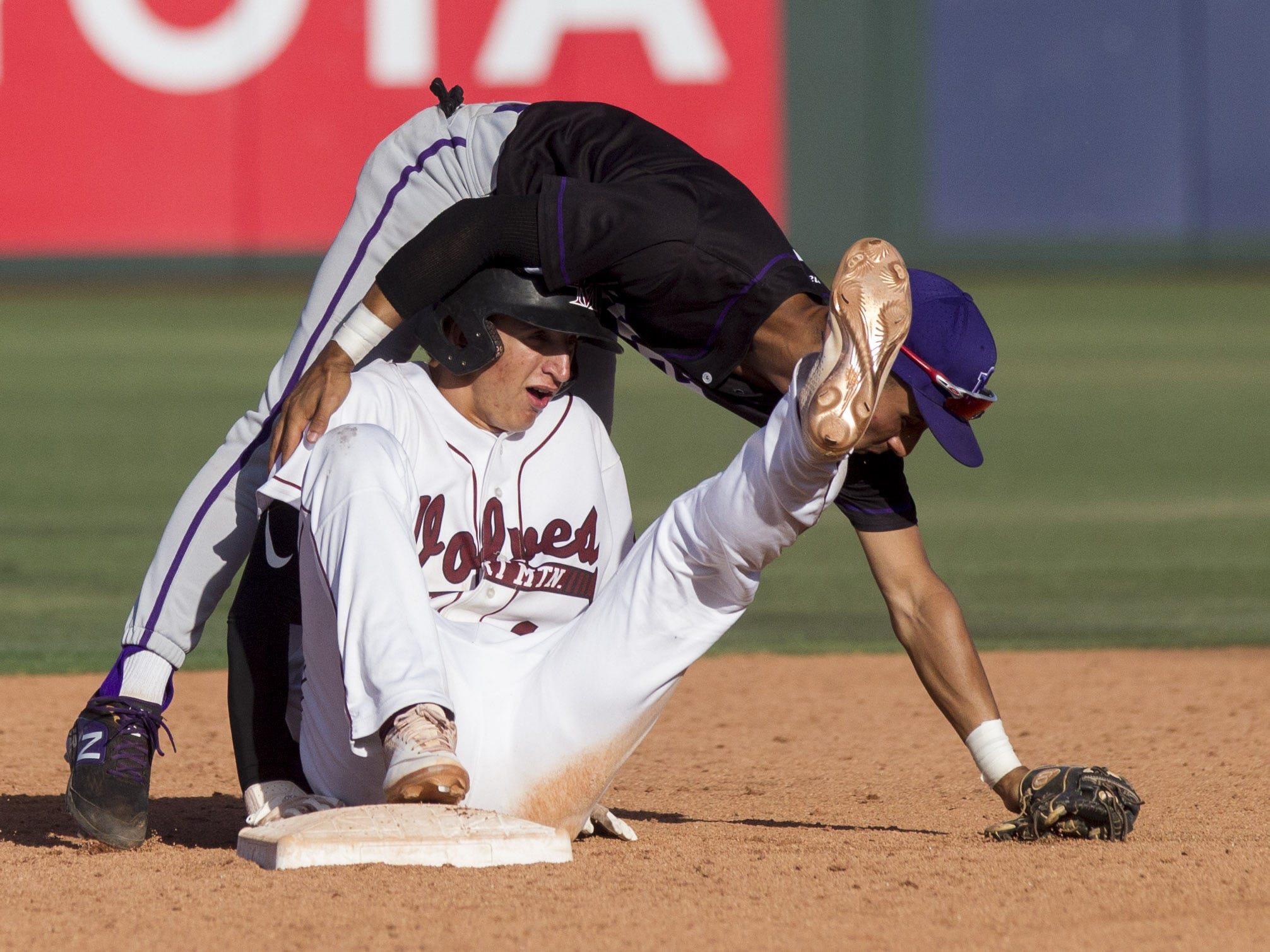 Sunrise Mountain's Andy Moreno catches himself after tripping over Desert Mountain's Zack Stewart at second base during the 5A state baseball second round at Diablo Stadium in Tempe, Arizona, April 29, 2019.