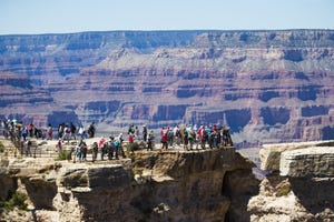 Visitors take in the view at Grand Canyon National Park from Mather Point, where railings mark the edge of the canyon's rim.