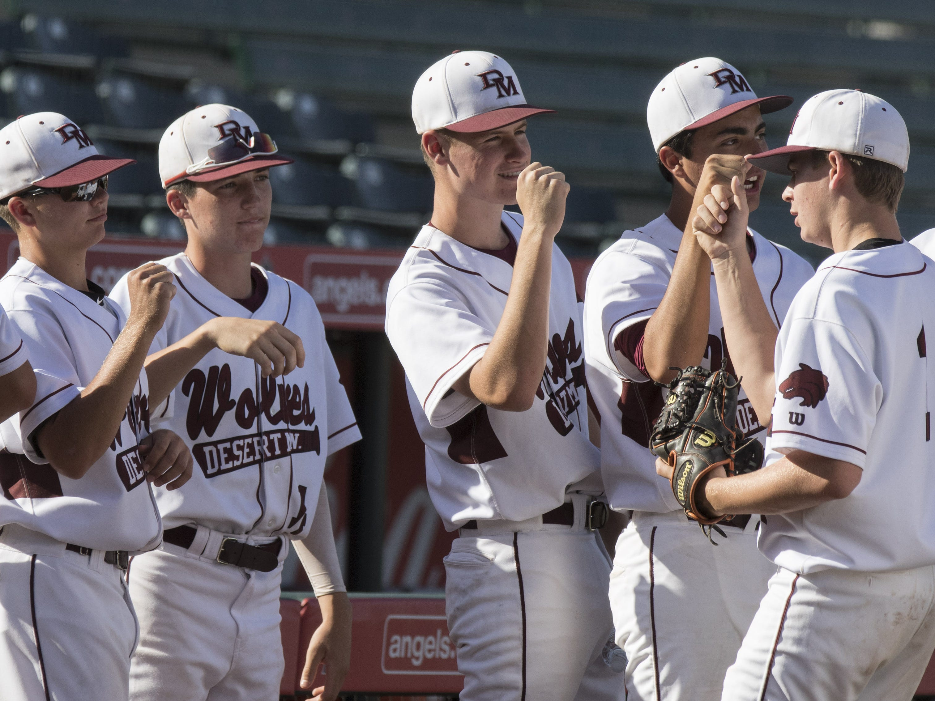 Desert Mountain pitcher Nick Suspenzi (1) is greeted by teammates after quick inning against Sunrise Mountain during the 5A state baseball second round at Diablo Stadium in Tempe, Arizona, April 29, 2019.