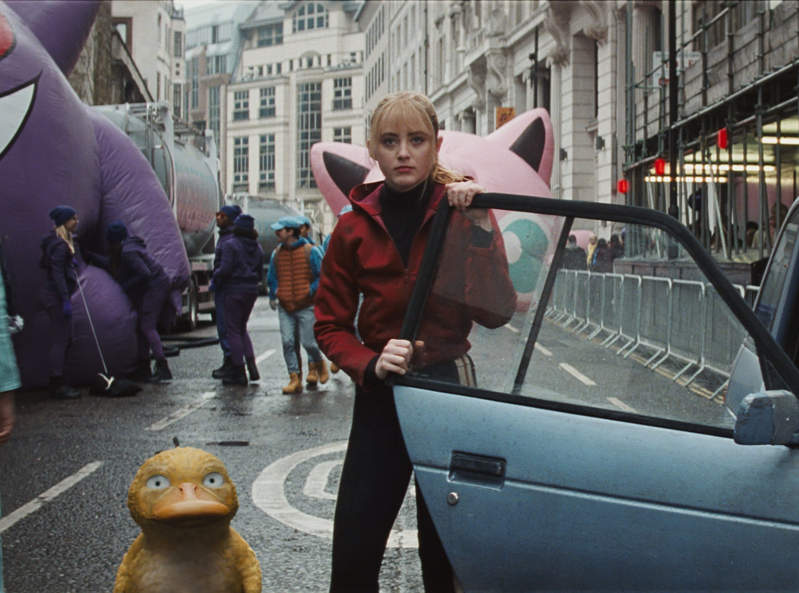 "Lucy (Kathryn Newton) and Psyduck arrive at the parade in Ryme City in ""Pokemon Detective Pikachu."""