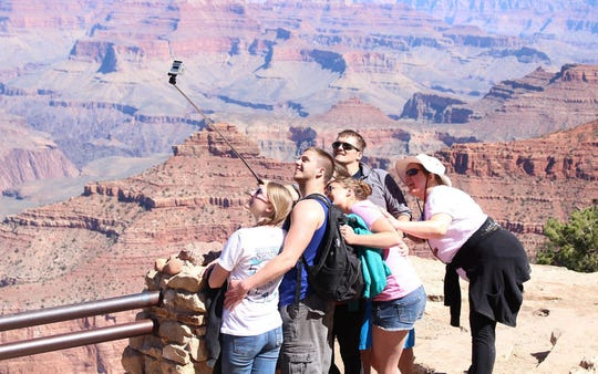 Tourists at Grand Canyon National Park pose for a group photo behind one of the railings at this overlook.