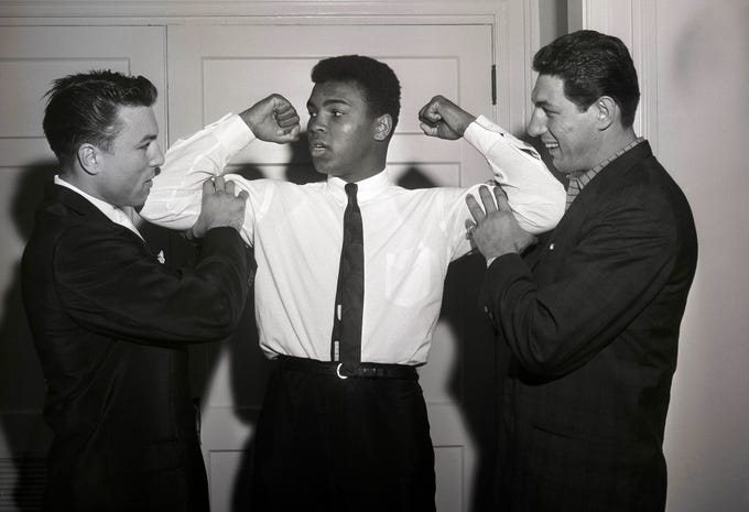 Cassius Clay, later known as Muhammad Ali,  center, poses with boxers Mike DeJohn and George Chuvalo at the Sheraton Hotel in Louisville.