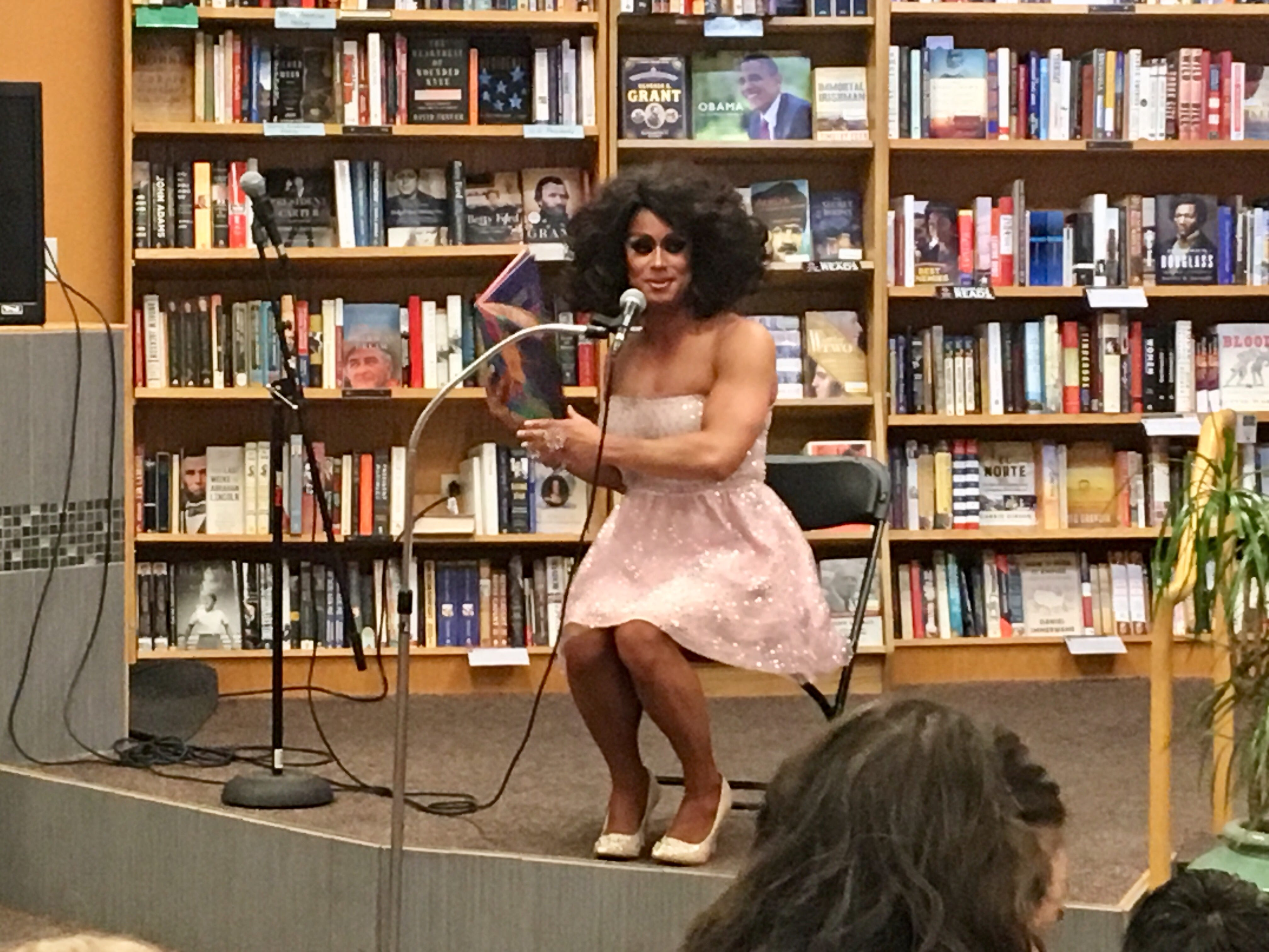 Drag queen Nevaeh McKenzie came on stage to read to kids at Changing Hands Bookstore in Tempe wearing a strapless glittery pink gown and high heels.