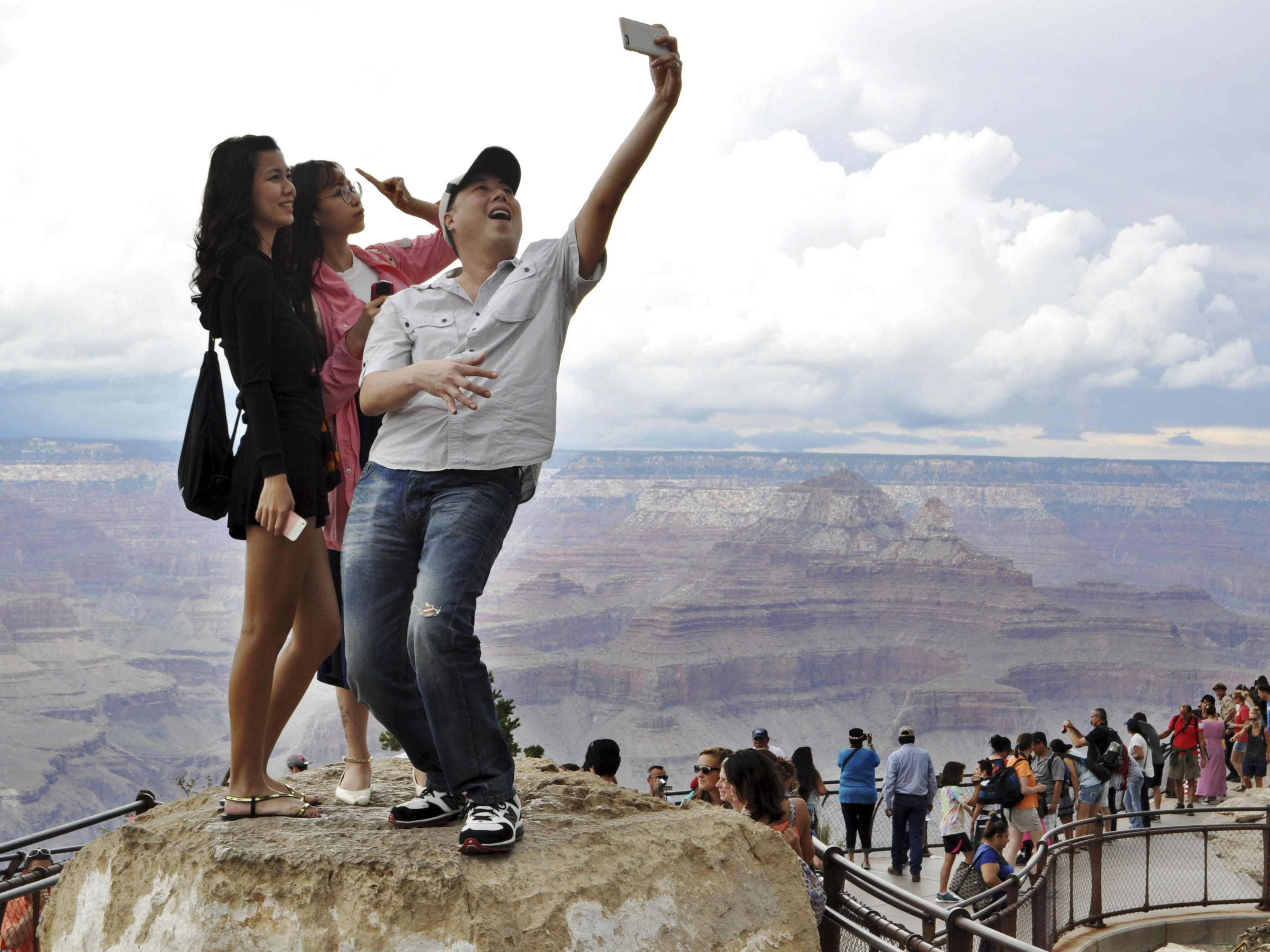 Tourists Joseph Lin, Ning Chao, center, and Linda Wang, left, pose for a selfie along the south rim at Grand Canyon National Park.