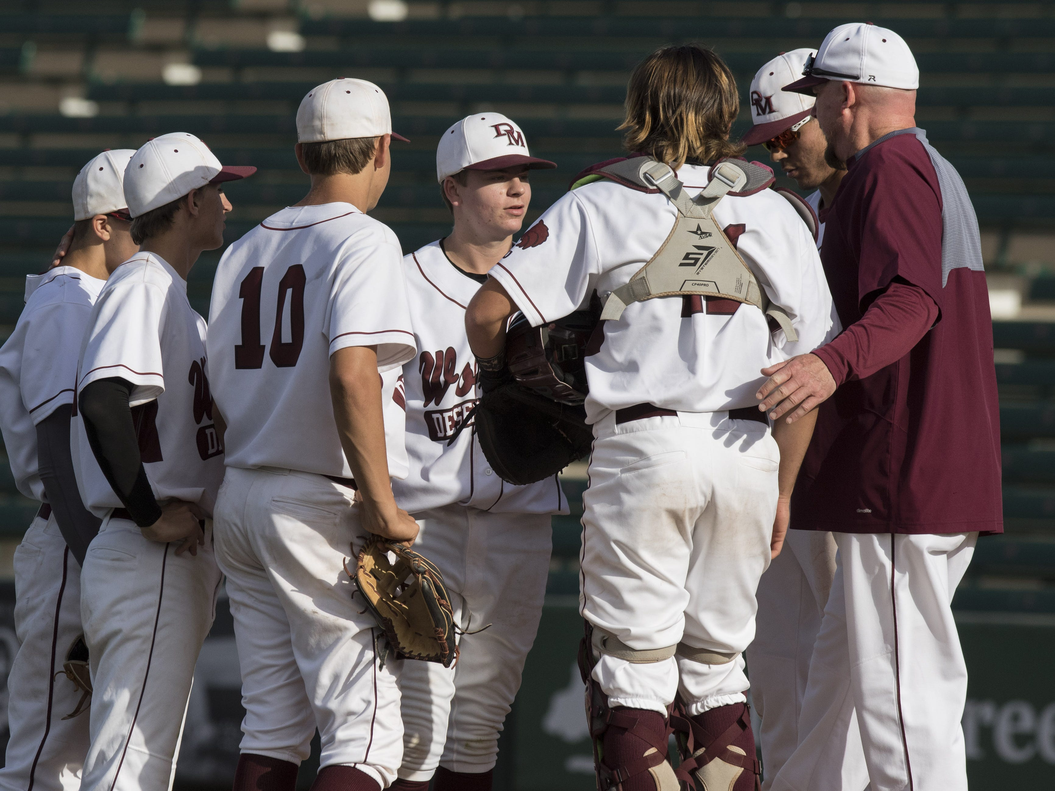 Desert Mountain coach Erik KehoeÊ (far right) talks to his team as they play Sunrise Mountain during the 5A state baseball second round at Diablo Stadium in Tempe, Arizona, April 29, 2019.