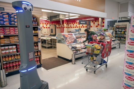 From the left, Lindsey Strine says that her her children Reagan, 2, and Audrey, 4, look for where Marty is around the store once they figured out it wasn't going to hurt them at the Giant supermarket in York Township. Marty robots are being introduced in all Giant stores.