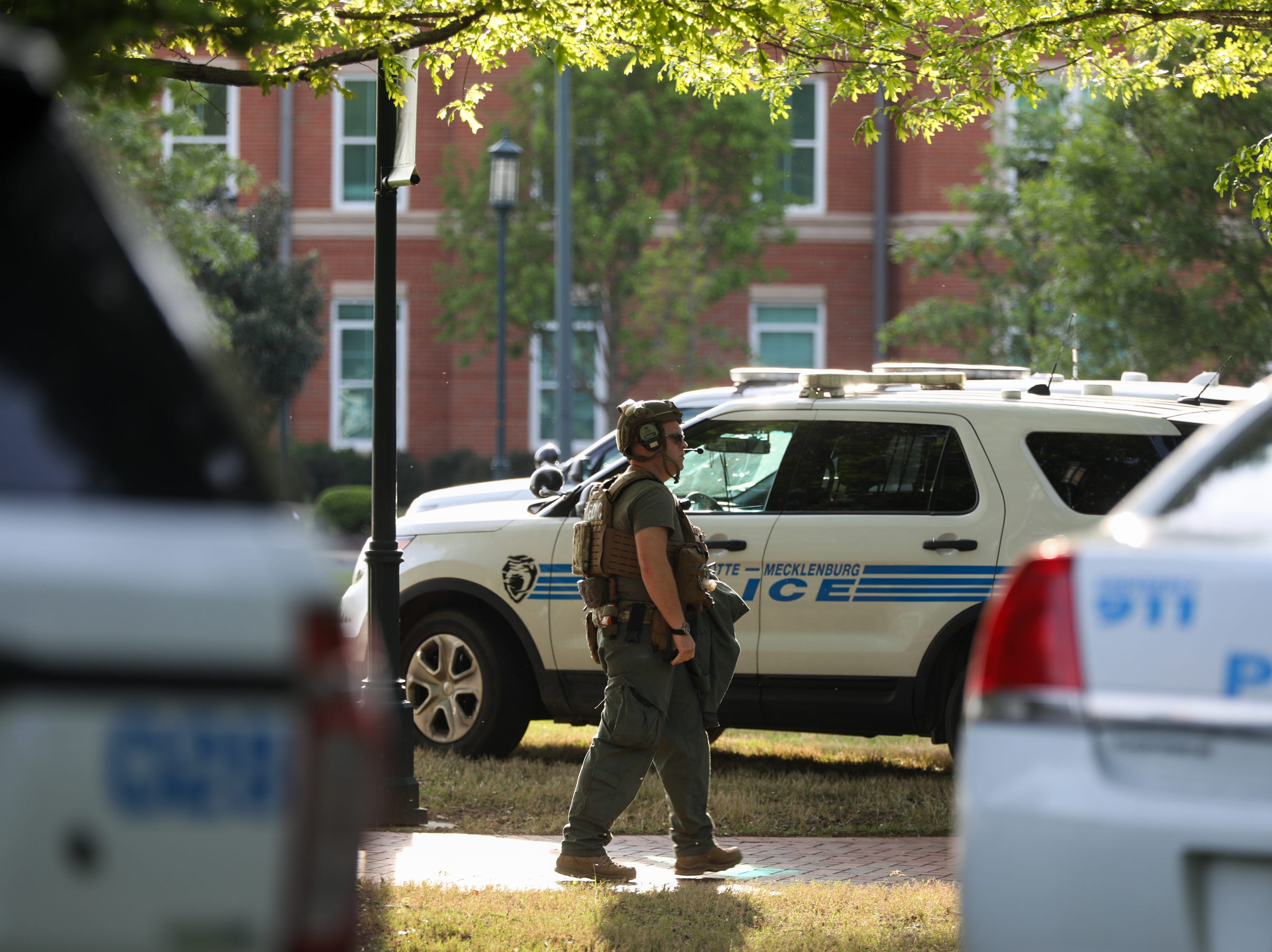 A medic walks between police cars after a shooting on the campus of University of North Carolina Charlotte in University City, Charlotte, on April 30, 2019. - Six people were shot, two of them died on the University of North Carolina Charlotte campus. One person was taken into custody, according to police sources.