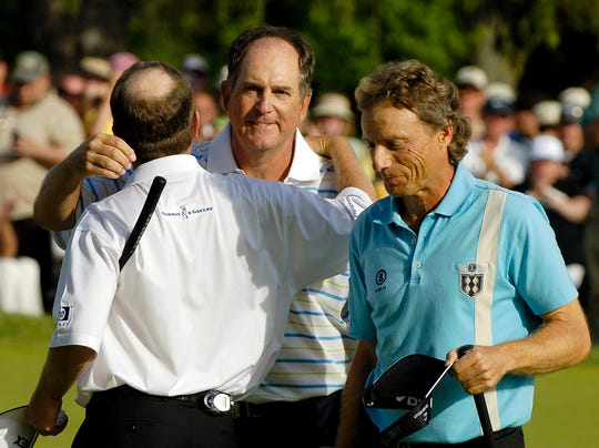 Jay Haas, center, is congratulated by Jeff Sluman, left, as Bernhard Langer, of Germany, walks past on the 18th green at the Oak Hill Country Club.