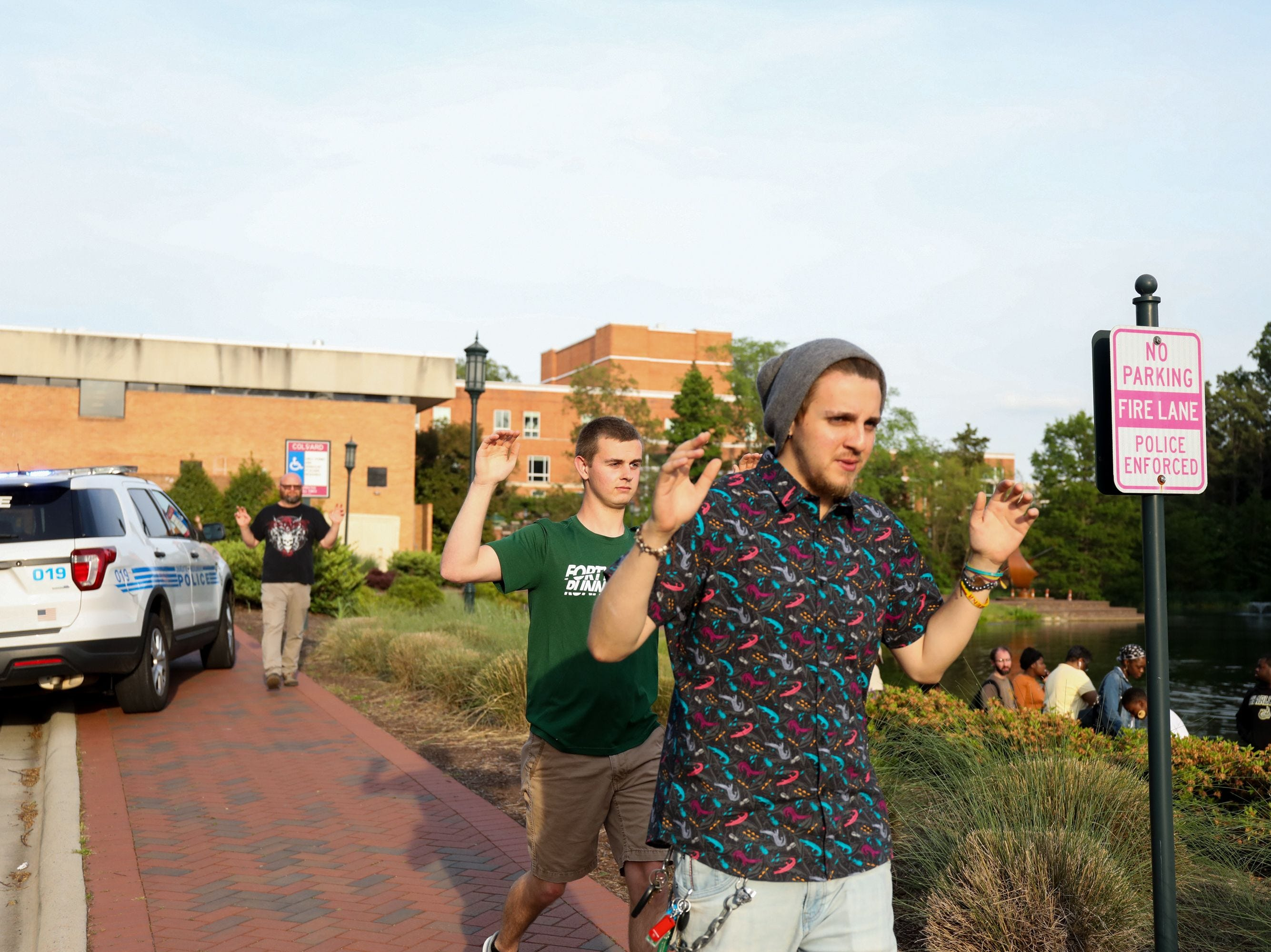 Students and faculty file out of buildings with their hands up during a lockdown after a shooting on the campus of University of North Carolina Charlotte in University City, Charlotte, on April 30, 2019. - Six people were shot, two of them died on the University of North Carolina Charlotte campus. One person was taken into custody, according to police sources.
