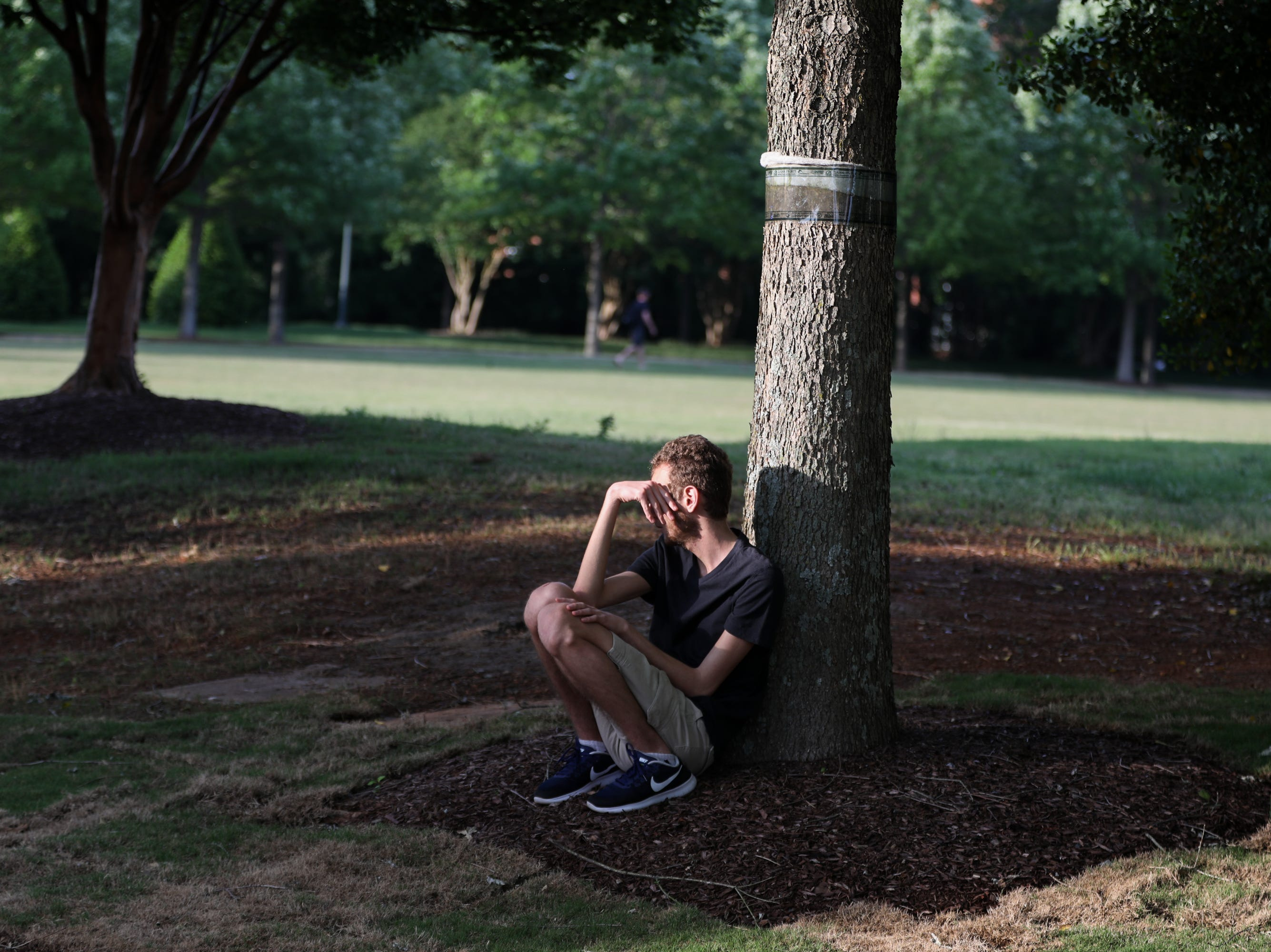 A student sits under a tree after a shooting on the campus of University of North Carolina Charlotte in University City, Charlotte, on April 30, 2019. - Six people were shot, two of them died on the University of North Carolina Charlotte campus. One person was taken into custody, according to police sources.