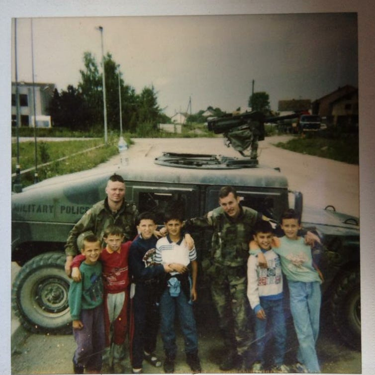 Army Sgt. Sean Halverson, right, takes a moment from military police duty in Bosnia in the mid-1990s to pose for a photo with some of the local children.