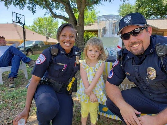 Harley Ratliff poses with two San Angelo Police officers at her lemonade stand Sunday, April 28, 2019.
