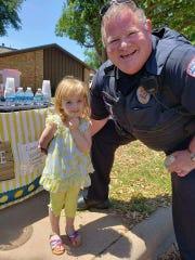 Harley Ratliff poses with a San Angelo police officer after selling him lemonade Sunday, April 28, 2019.