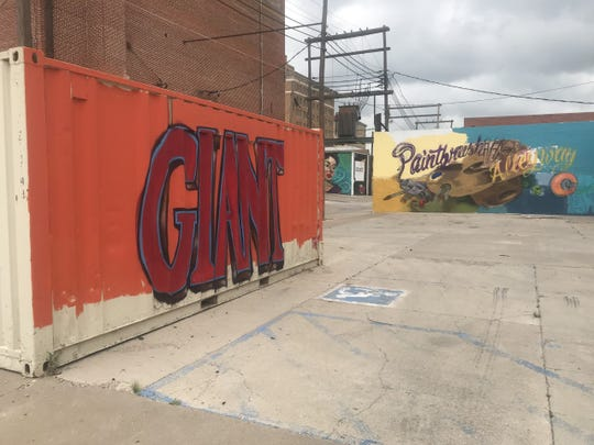 "The movie title ""Giant"" painted on a crate of sorts opens up the presentation of Paint Brush Alley between the Texas Theatre and Firestone on Concho Ave."