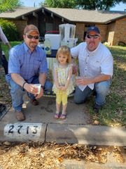 Harley Ratliff poses with Police chief Frank Carter and another man at her lemonade stand Sunday, April 28, 2019.