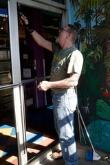 Andy Miller with Miller Glass scrapes excess glass from the front door at Cabo's restaurant on Tuesday, April 30, 2019.