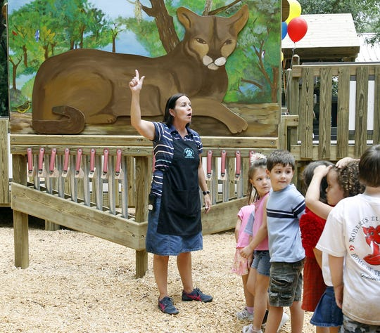 Karen Gay, pre-school director at the Tallahassee Museum gathers up her class in front of a large painting at the playground at the Tallahassee Museum in 2006.