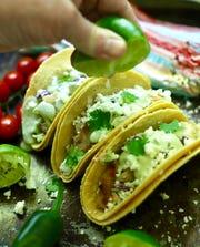 Avocado, fresh lime juice, cilantro and crema top these tasty fish tacos.