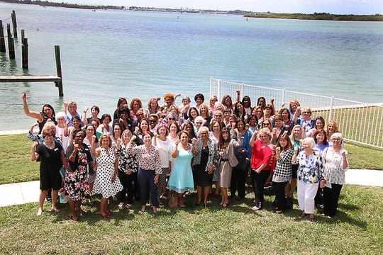 Impact 100 St. Lucie founding members pose as Rosie The Riveter at the Pelican Yacht Clubin Fort Pierce.