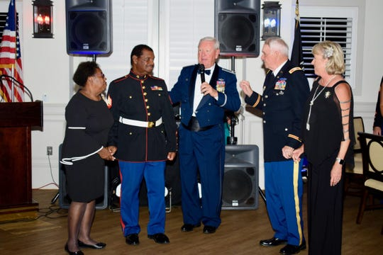 """Dorothy McIntosh, left, and her husband, Marine Corps Sgt. Sylvester McIntosh are congratulated by Air Force Col. Marty Zickert, Army Col. Sam Kouns and his wife, Linda Kouns, at the """"Stars &Stripes Spectacular Gala."""" Sgt. McIntosh was keynote speaker at the event."""