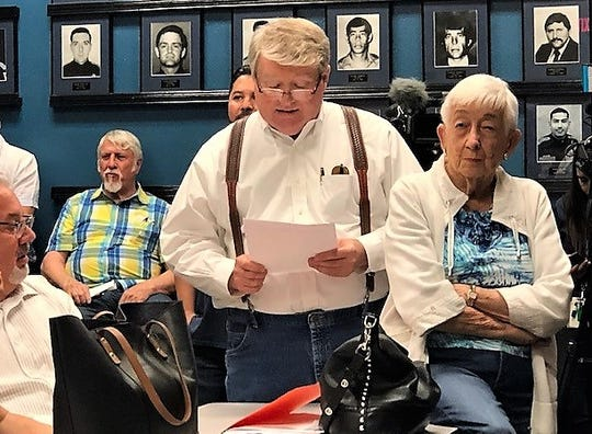 El Paso lawyer Charles Scruggs, who lives on the Vista Hills Country Club golf course, reads a petition asking the city to take over operation of the closing Vista Hills golf course at an April 29 meeting. Jeanne Lyons, a supporter of the petition and Vista Hills homeowner, listens.