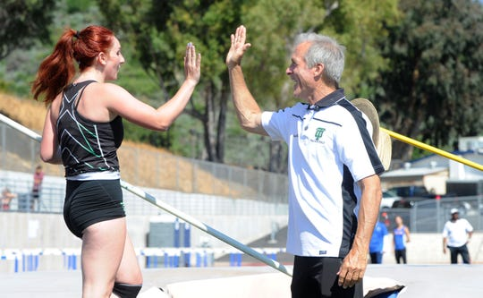 "Thousand Oaks High pole vault coach Kevin Burnett congratulates Giulia Colella after she cleared a height during the Marmonte League Track and Field Championships on April 26. ""It's so difficult, so technical, that it really takes a minimum of two years just to become a vaulter able to compete in a meet,"" Burnett says."
