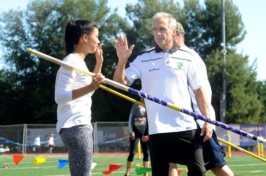 Thousand Oaks pole vault coach Kevin Burnett high-fives Seanne Chan during the Marmonte League finals on April 26.