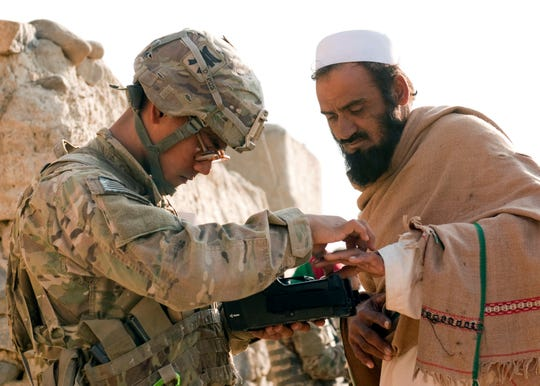 In this Nov. 5, 2012, photo provided by the U.S. Army, U.S. Army Pfc. Mark Domingo, left, takes an Afghan man's fingerprints in the village of Dande Fariqan, in Afghanistan's Khowst Province, as part of the military's effort to gather biometric data on the residents. Domingo, an Army veteran who converted to Islam and discussed launching various terror attacks throughout Southern California, was arrested as he plotted to bomb a white supremacist rally as retribution for the New Zealand mosque attacks, federal prosecutors said Monday.