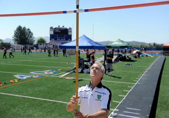 Thousand Oaks High pole vault coach Kevin Burnett sets up the station at the Marmonte League Track and Field Championships on April 26. Burnett, who competes in the pole vault at the Masters level, has coached several top pole vaulters at Thousand Oaks.