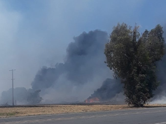 Smoke fills the air around a fire near Paige Avenue and I Street in Tulare on Tuesday, April 30, 2019.