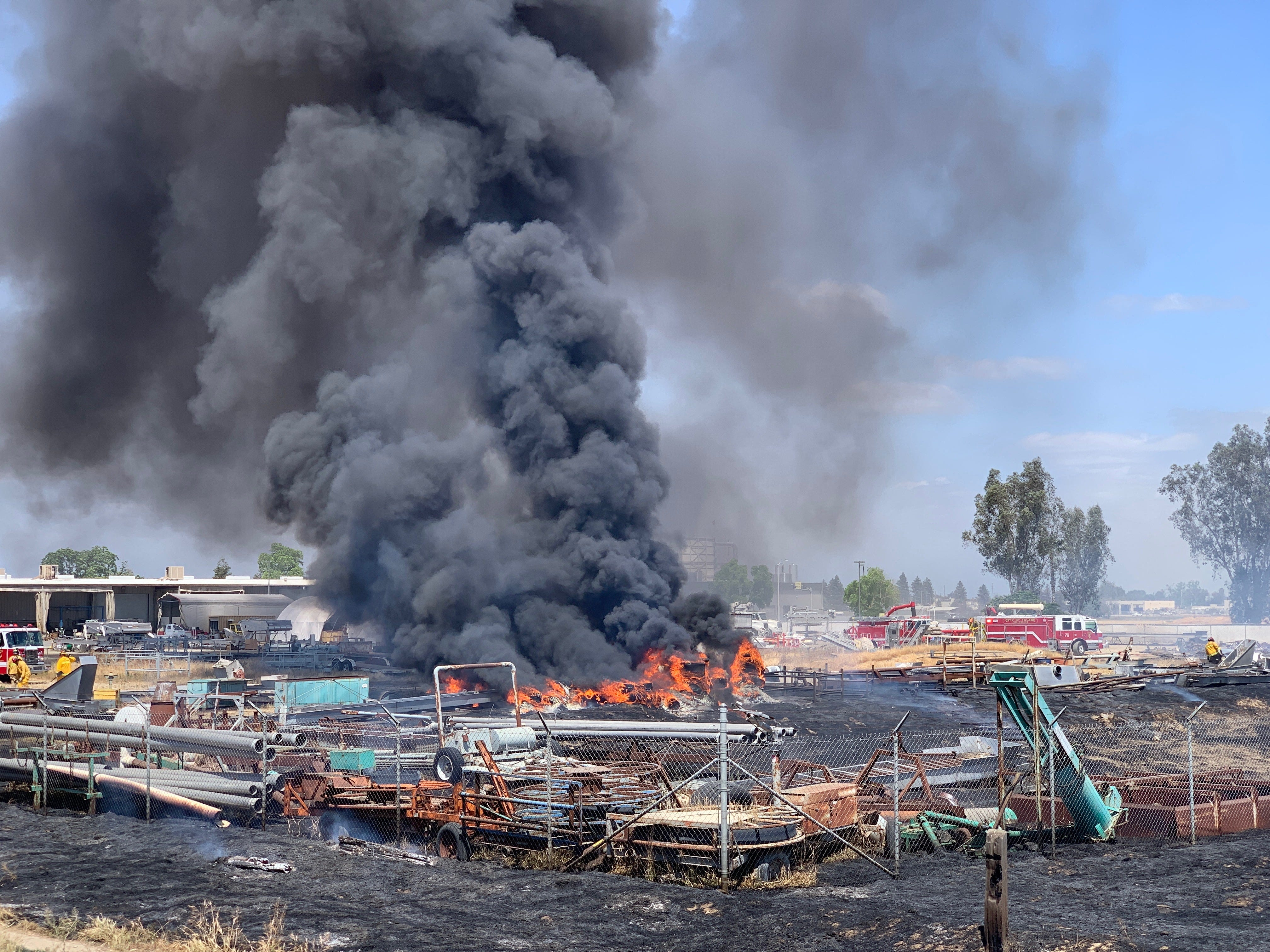 """A fire blazes near Paige Avenue and """"I"""" Street in Tulare on Tuesday, April 30, 2019."""