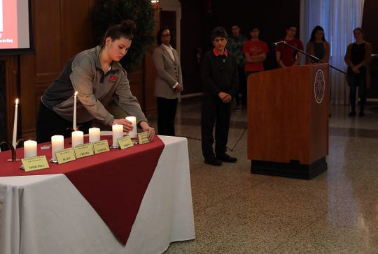 Iona College student lights a candle to remember those who lost their lives at Auschwitz concentration camp during a lecture series withÊPeter Hayes ofÊNorthwestern University, a leading expert on the Holocaust at Iona College in New Rochelle April 29, 2019.