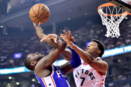 James Ennis draws a foul as he drives to the basket against Raptors guard Kyle Lowry during Monday's playoff game.
