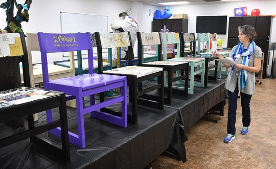 Wichita Falls Public Library Administrator Jana Hausburg checks through some of the 40 art chairs that will be part of the Chair-ity Art Auction to raise money for new seating in the children's department.