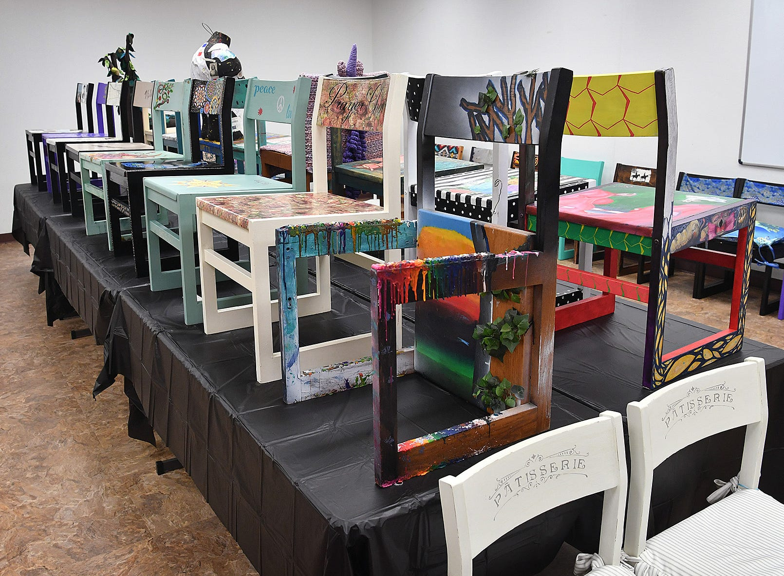 Art chairs for the Wichhita Falls Public Library's Chair-ity Art Auction include paint, fabrics, decoupage, melted crayons and more.