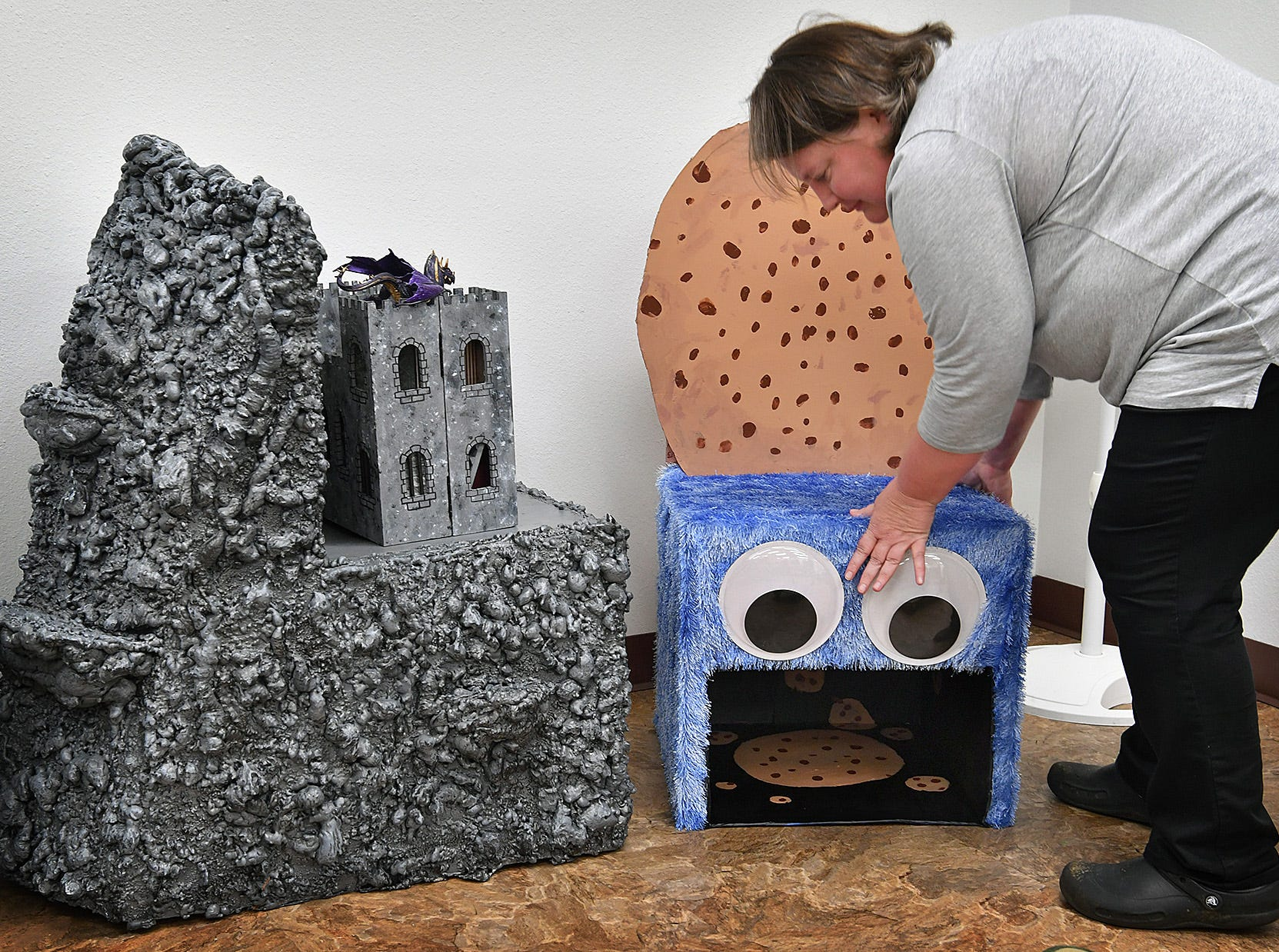 Jamie Dollar positions a Cookie Monster chair by Kathryn Simmerman next to a Castle Mountain chair created by Audrey Simmerman during set up for an artist reception with the Wichita Falls Public LibraryChair-ity Art Auction.