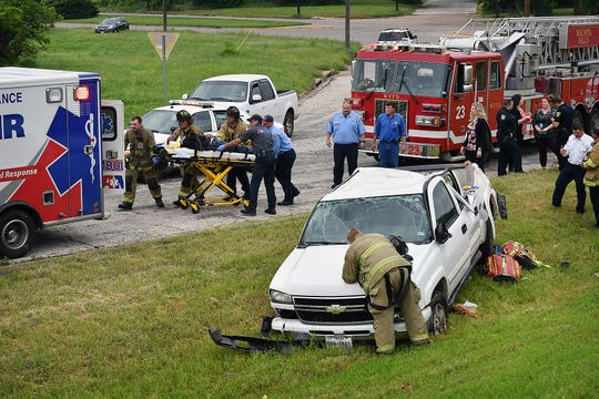 Emergency medical personnel prepare to transport the driver of a Chevrolet pickup truck that rolled down the embankment of the Emmanuel Davis Overpass at Martin Luther King Jr. Drive Tuesday morning.