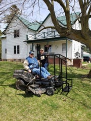 Bob on his mower with his engineer son, Russ, checking to see if his creation is working properly.