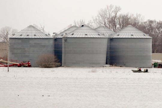 Utility workers travel by boat past grain bins in the flooded town of Pacific Junction, Iowa.