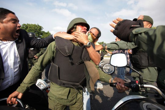 Opponents to Venezuela's President Nicolas Maduro, behind and left, scuffle with a Bolivarian National Guard officer who is loyal to President Nicolas Maduro during clashes with rebel soldiers and anti-government protesters outside La Carlota military airbase in Caracas, Venezuela, Tuesday, April 30, 2019. Venezuelan opposition leader Juan Guaidó and jailed opposition leader Leopoldo Lopez took to the streets with a small contingent of heavily armed troops early Tuesday in a bold and risky call for the military to rise up and oust Maduro. (AP Photo/Boris Vergara)
