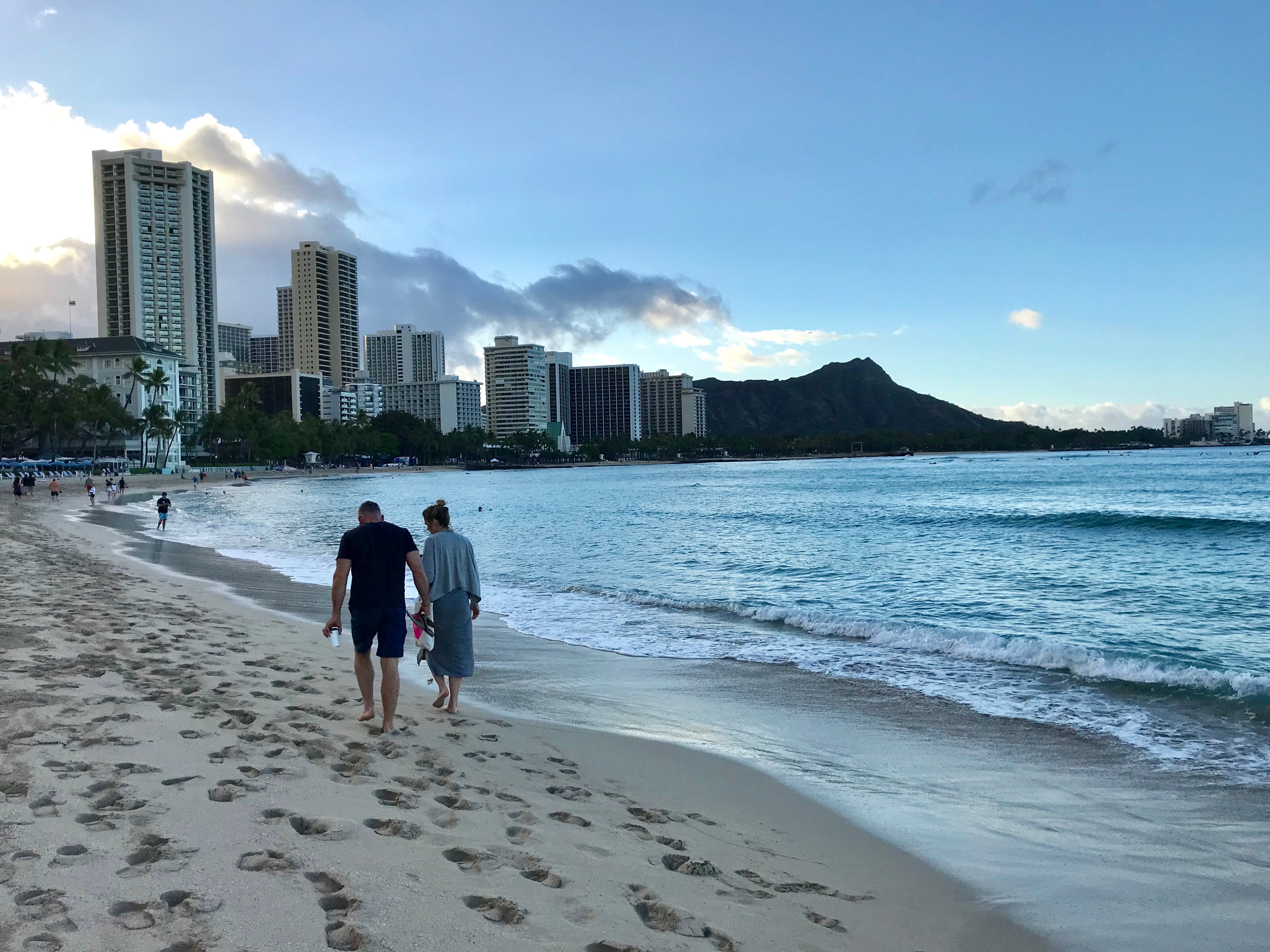 Sunrise at iconic Waikiki Beach, with Diamond Head in the distance.