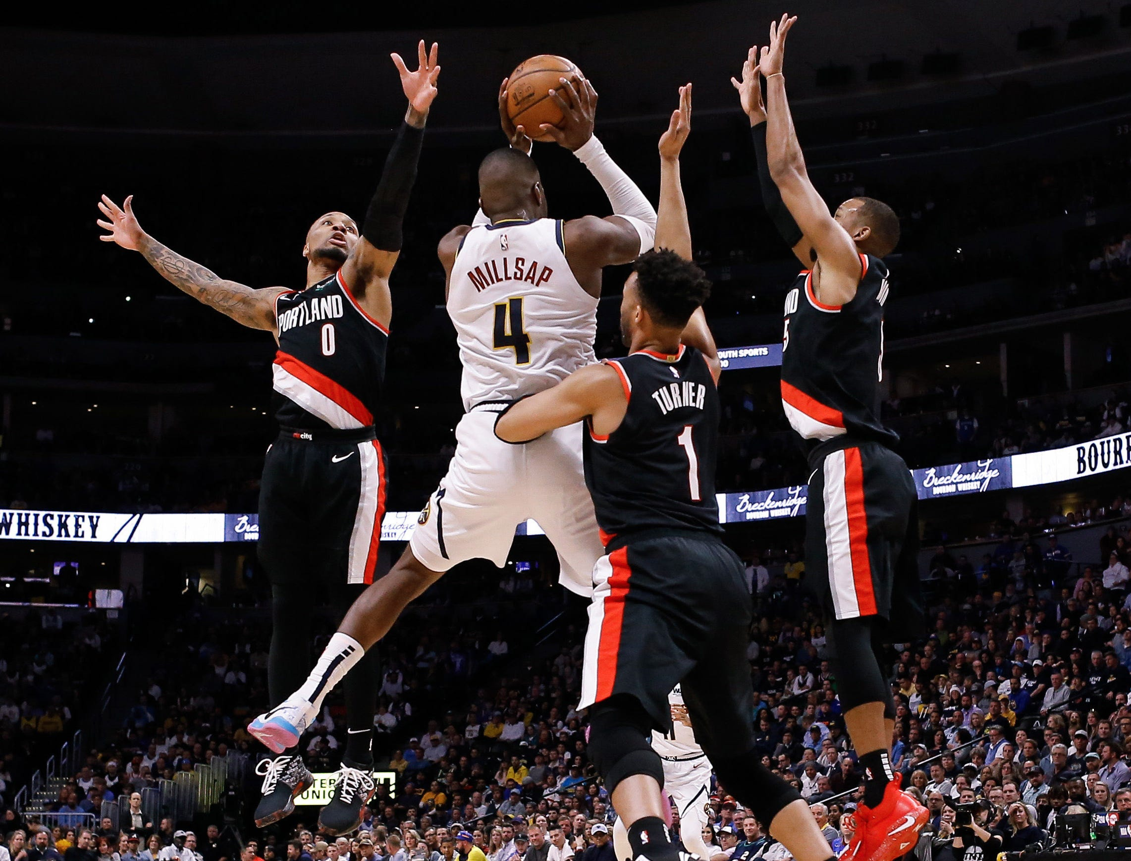 April 29: Nuggets forward Paul Millsap (4) tries to pas out of the triple-team by Trail Blazers defender Damian Lillard (0), Evan Turner (1) and Rodney Hood (5) during Game 1.