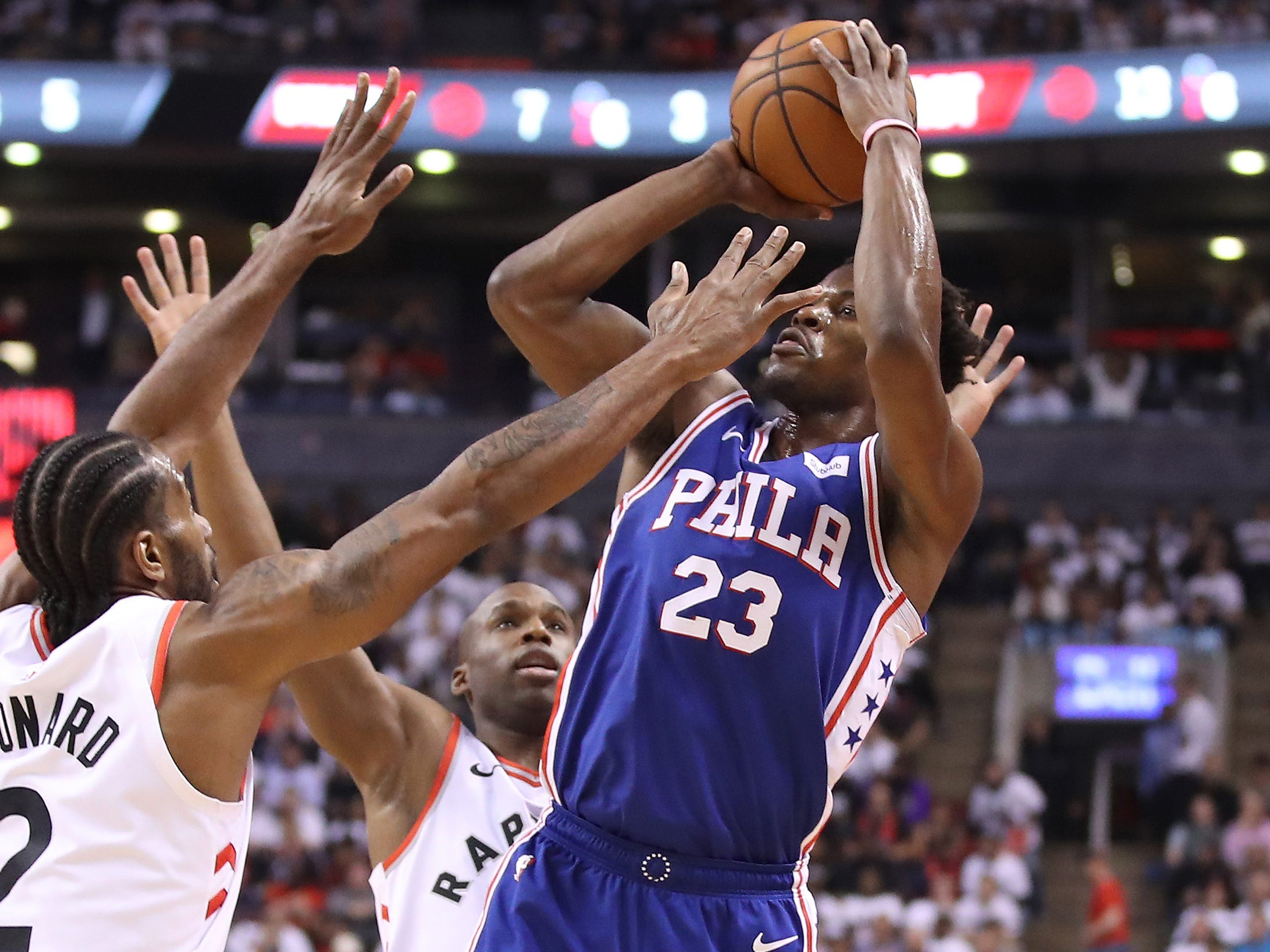 April 29: Sixers guard Jimmy Butler (23) takes the tough shot over Raptors defender Kawhi Leonard (2) during Game 2 in Toronto.