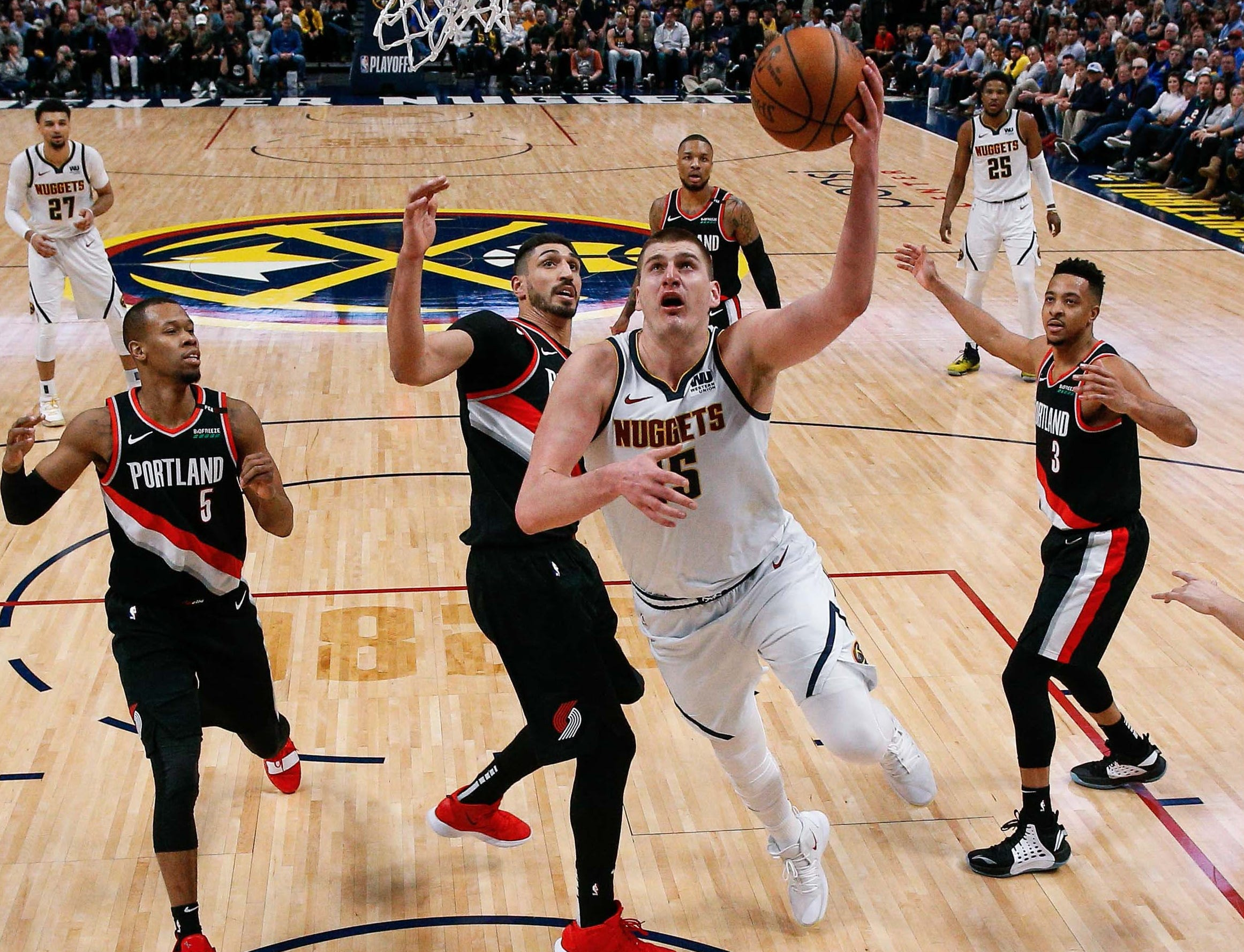 April 29: Nuggets center Nikola Jokic (15) makes a move to the basket past Trail Blazers defenders Rodney Hood (5) and Enes Kanter during Game 1 in Denver.