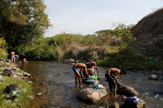 Central American migrants traveling in a caravan headed to the U.S. border wash clothes and take baths in a river on a rest day near Mapastepec in Chiapas state, Mexico, Sunday, April 21, 2019. The outpouring of aid that once greeted Central American migrants as they trekked in caravans through southern Mexico has been drying up, so this group is hungrier, advancing slowly or not at all, and hounded by unhelpful local officials. (AP Photo/Moises Castillo)