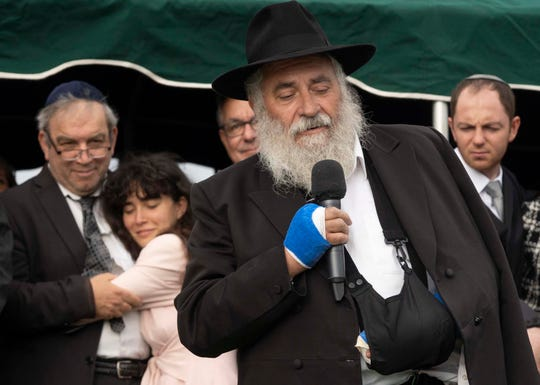 Rabbi Yisroel Goldstein speaks while Hannah Kaye hugs her father, Howard Kaye, while her mother Lori Kaye, was laid to rest at El Camino Memorial Park Cemetery on April 29, 2019.