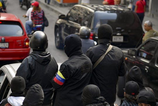 """Masked members of a """"colectivo,"""" or pro-government cells, attend a rally in Caracas on January 7, 2019. - """"Colectivo"""" members are referred to as both, revolutionary idealists and thugs."""