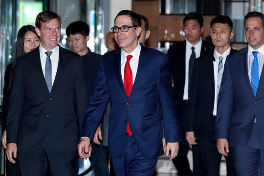 U.S. Treasury Secretary Steven Mnuchin, center, is escorted by bodyguards and officials as he arrives at a hotel in Beijing, Tuesday, April 30, 2019. Mnuchin arrived in China's capital to hold a new high-level trade talks with China on May 1.